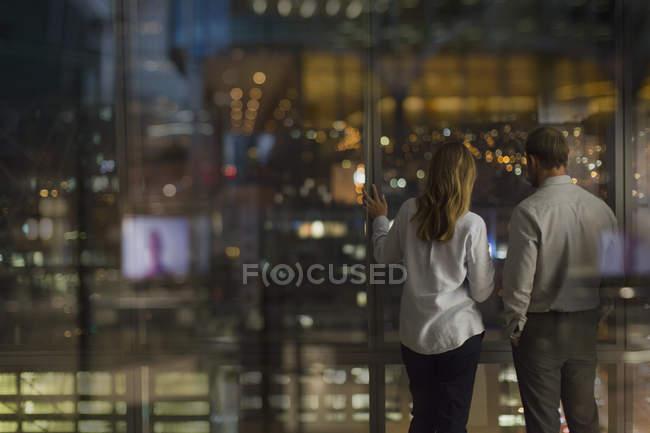 Homme d'affaires et femme d'affaires regardant par la fenêtre du bureau urbain la nuit — Photo de stock