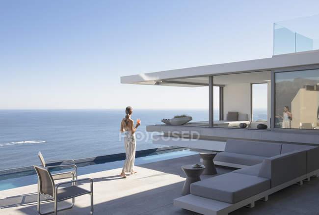 Frau auf moderne, Luxus home Schaufenster außen Sonnenterrasse mit Meerblick — Stockfoto