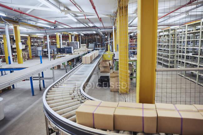 Картонные коробки на конвейере в распределительном складе — стоковое фото