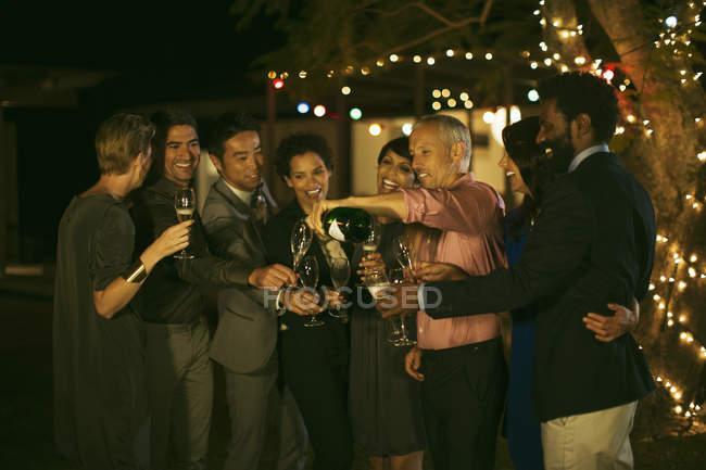 Freunde feiern mit Champagner auf party — Stockfoto
