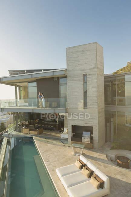 Couple standing on sunny modern luxury home showcase balcony over lap pool — Stock Photo