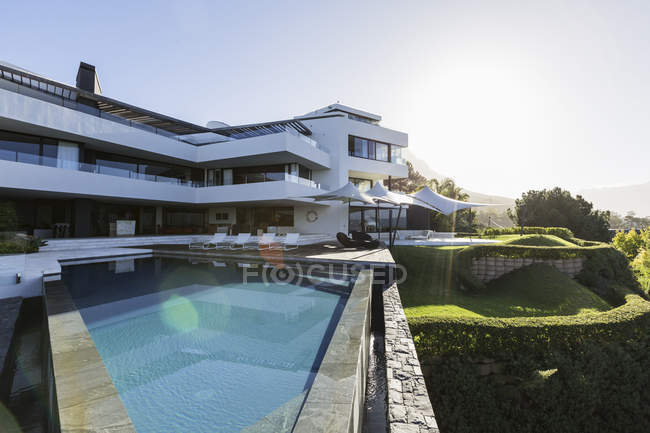 Sunny modern luxury home showcase exterior with infinity pool — Stock Photo