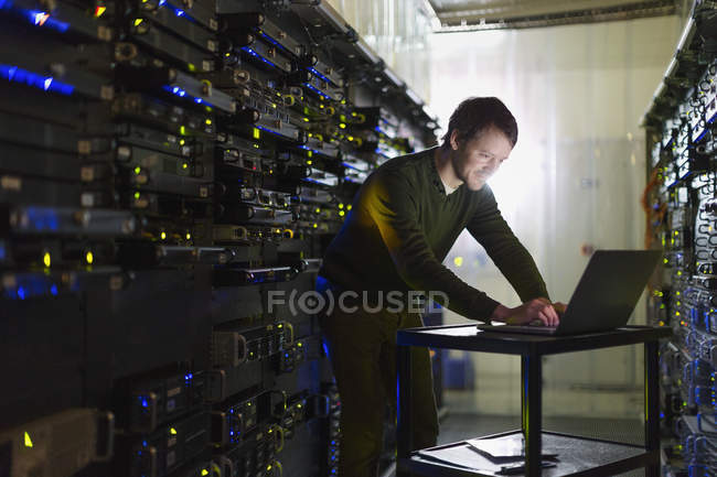Server room technician working at laptop — Stock Photo
