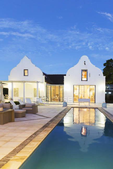 Розкішний будинок і lap басейн, освітлені вночі — стокове фото