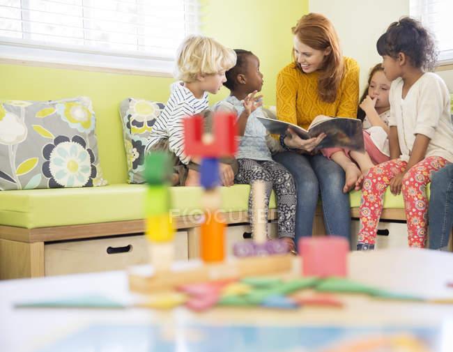 Enseignant et élèves lecture en salle de classe — Photo de stock