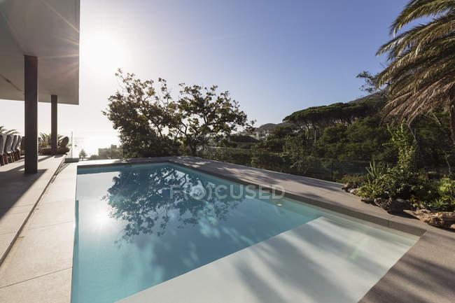 Soleggiata, tranquilla piscina in grembo circondata da alberi — Foto stock