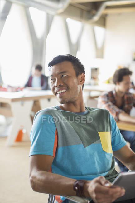 Счастливый случайные бизнесмен, глядя через плечо в офисе — стоковое фото