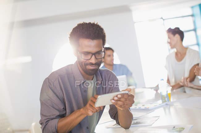 Uomo d'affari creativo che utilizza lo smartphone nella riunione della sala conferenze — Foto stock