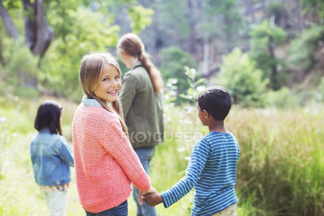 Children holding hands in field — Stock Photo