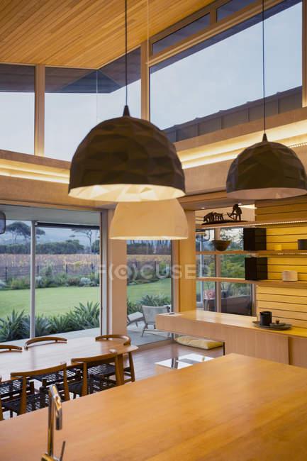 Illuminated modern pendants hanging over wood kitchen island — Stock Photo