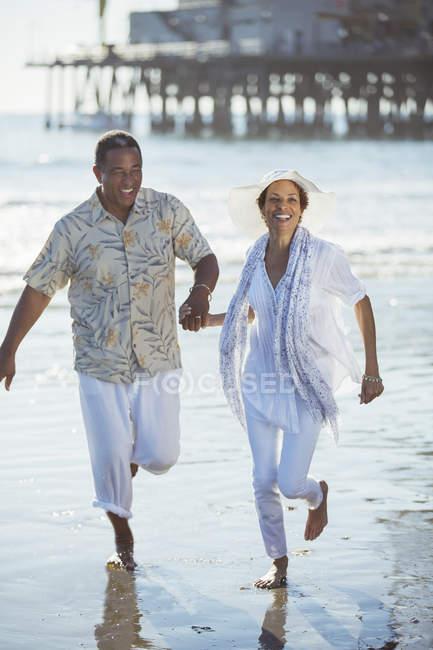 Sorridente coppia di anziani in esecuzione sulla spiaggia soleggiata — Foto stock