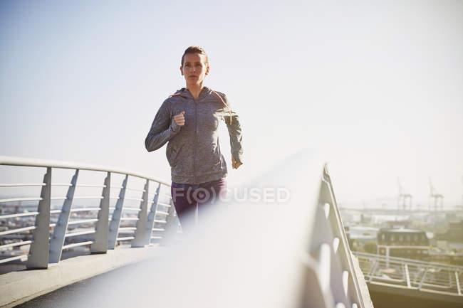 Corredor femenino corriendo en soleada pasarela urbana - foto de stock