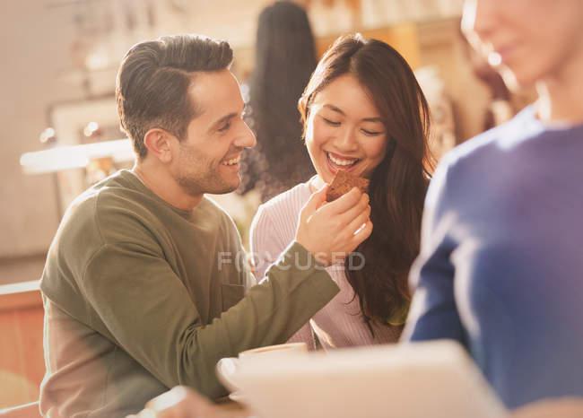 Novio alimentación brownie a novia en café - foto de stock