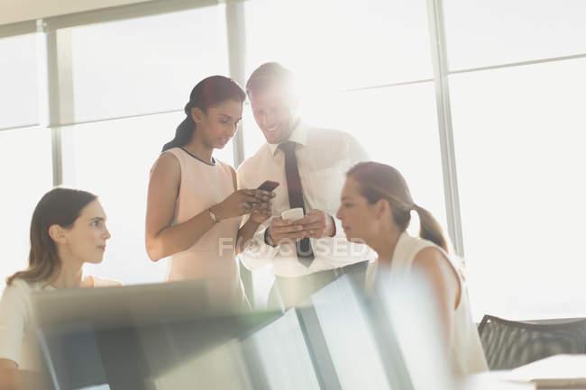 Mensagens de pessoas de negócios com celulares em reunião numa sala de conferência ensolarado — Fotografia de Stock