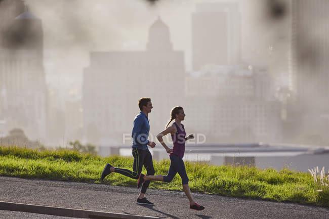 Corredor pareja corriendo en la soleada acera urbana de la ciudad - foto de stock