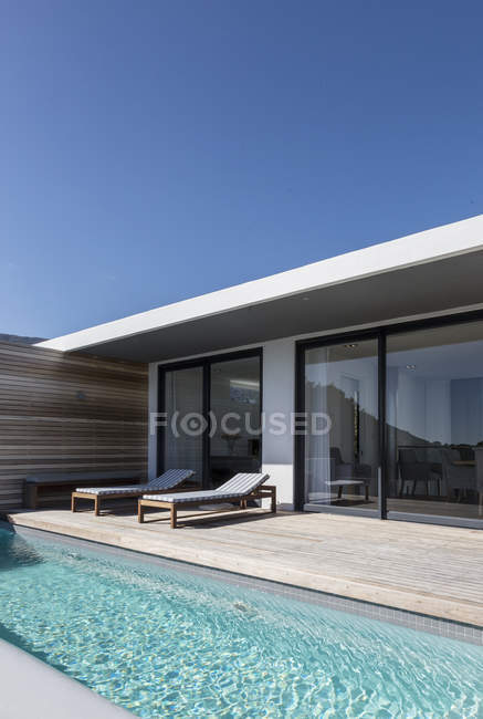 Sunny casa di lusso moderna vetrina patio esterno e piscina sul giro — Foto stock
