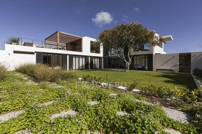 Sonnigen Luxus modern home Schaufenster Exterieur mit sonnigen Garten und Baum — Stockfoto
