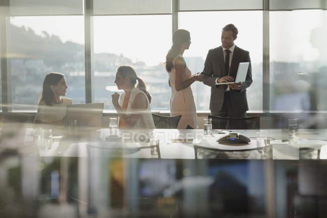 Gli uomini d'affari parlando, utilizzando il computer portatile in sala conferenze riunione — Foto stock