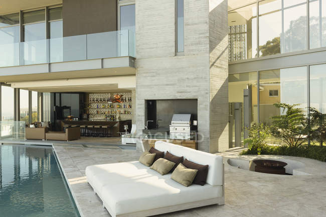 Luxury home showcase exterior patio with chaise lounges at poolside — Stock Photo