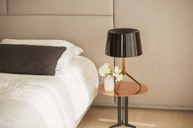 Lamp and rose bouquet on bedside table — Stock Photo