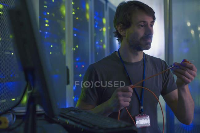 Technicien de salle de serveur examinant le câble à l'ordinateur — Photo de stock