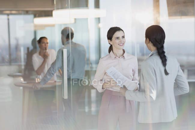 Empresarias con papeleo hablando en oficina - foto de stock