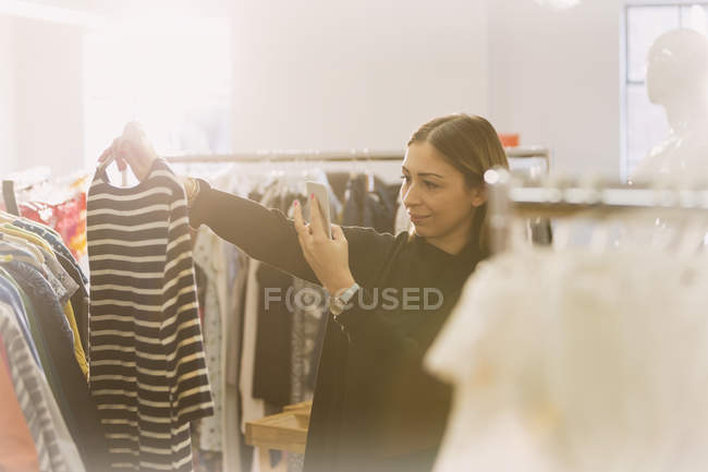 Fashion buyer photographing striped shirt — Stock Photo