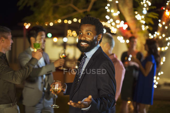 Man gesturing with wine at party — Stock Photo