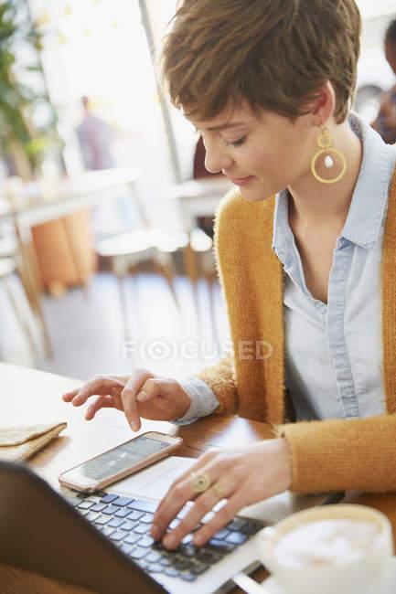 Geschäftsfrau im Café mit Smartphone und laptop — Stockfoto