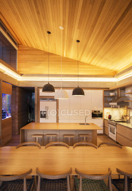 Illuminated slanted wood ceiling over luxury kitchen and dining table — Stock Photo