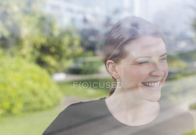 Усміхається жінка дивиться вікно в сучасному офісі — стокове фото