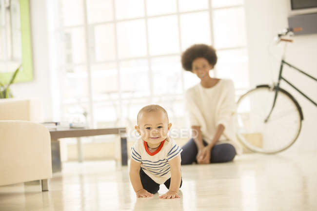 Mother watching baby boy crawl on living room floor — Stock Photo