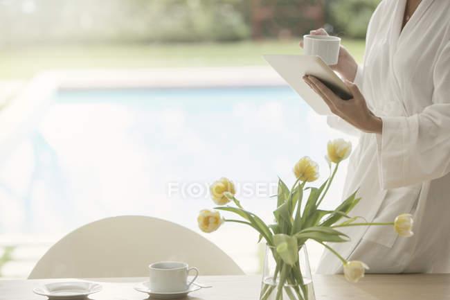 Donna in accappatoio bere caffè e utilizzando tablet digitale a bordo piscina — Foto stock