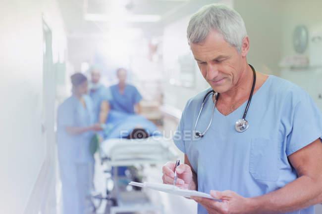 Chirurgien homme mûr examen dossier médical presse-papiers dans le couloir de l'hôpital — Photo de stock