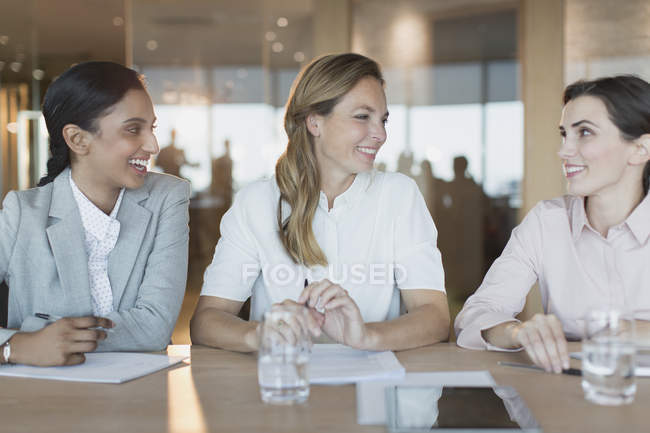 Smiling businesswomen talk in conference room meeting — Stock Photo