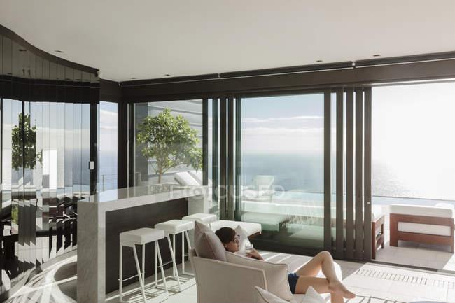 Mulher relaxante na moderna sala de estar com vista para o oceano — Fotografia de Stock