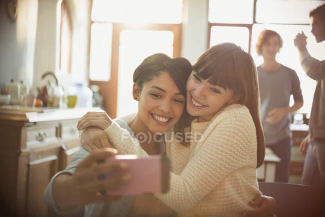 Amici delle giovani donne prendendo selfie con la fotocamera del telefono in appartamento — Foto stock