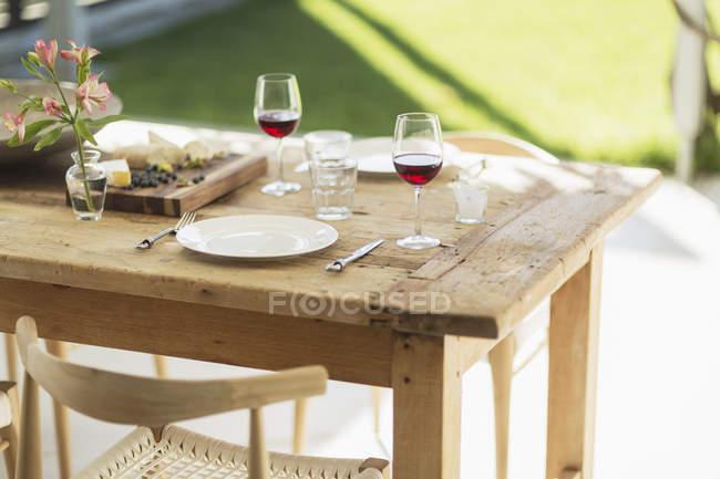 Вино і закуска на дерев'яні обідній столику на внутрішній дворик — стокове фото