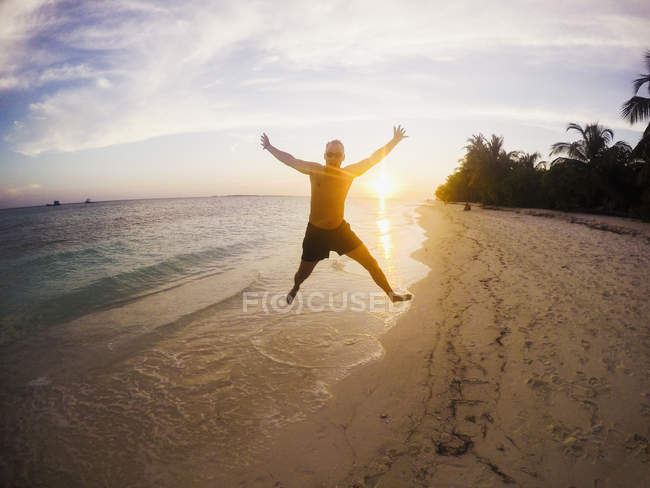 Portrait of exuberant man jumping on tropical beach at sunset — Stock Photo