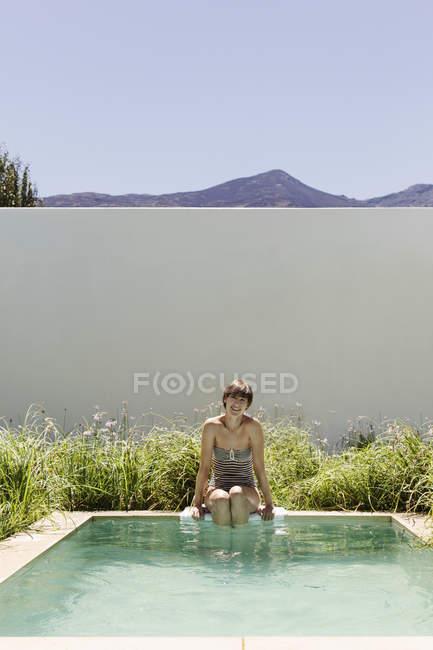 Woman dipping legs in luxury lap pool — Stock Photo