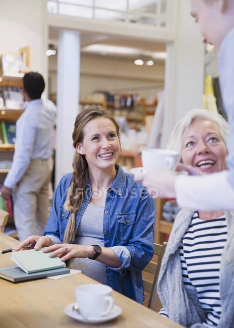 Бариста подает кофе матери и дочери в кафе — стоковое фото