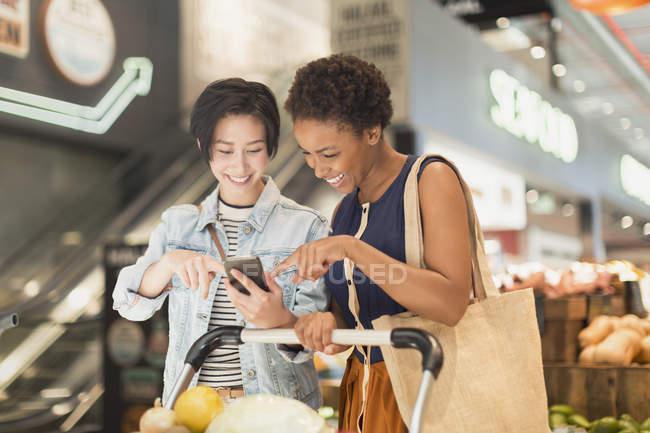 Giovane coppia lesbica utilizzando il telefono cellulare, negozi di alimentari nel mercato — Foto stock