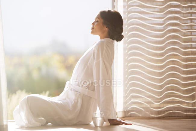Спокойная женщина в халате сидит скрестив ноги у солнечных дверей — стоковое фото