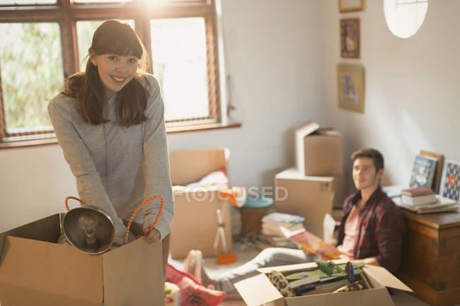 Ritratto sorridente giovane coppia in movimento disimballaggio scatole in appartamento — Foto stock