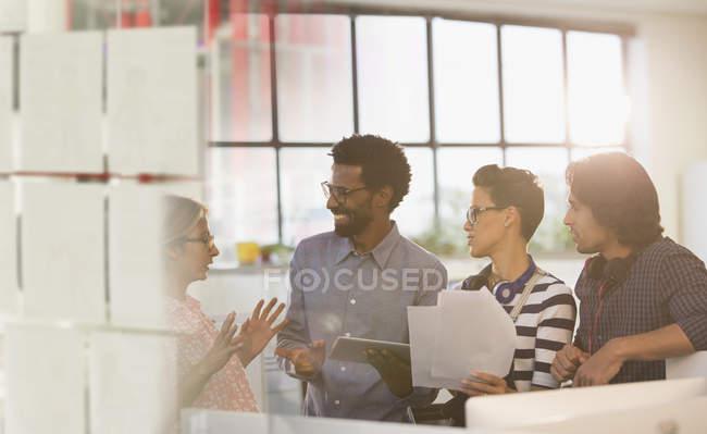 Sonriente creativos empresarios en reunión de la oficina de intercambio de ideas - foto de stock