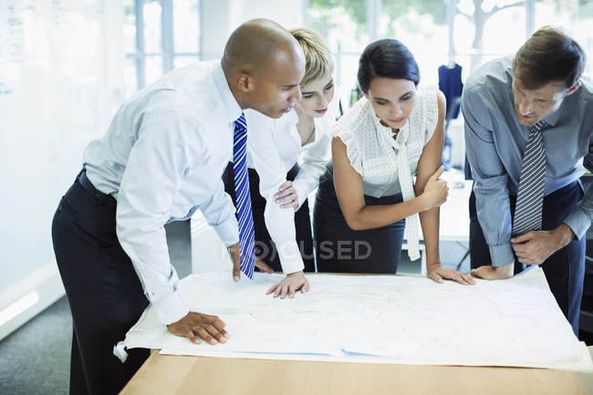 Business people examining blueprints in office — Stock Photo