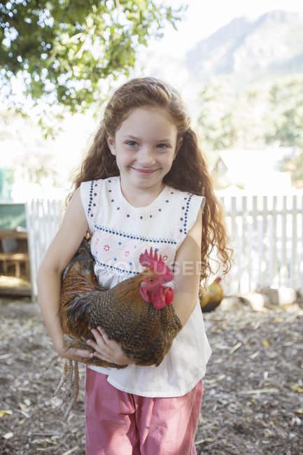 Ragazza che tiene il pollo al petting zoo — Foto stock