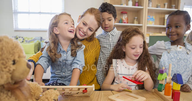 Students and teacher playing in classroom — Stock Photo
