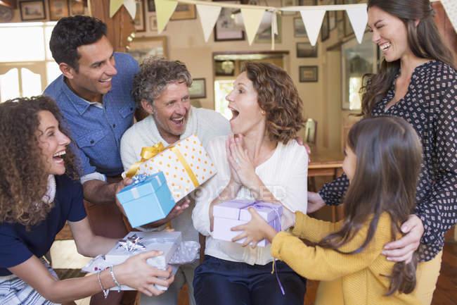 Mujer mayor que recibe un regalo de la familia - foto de stock