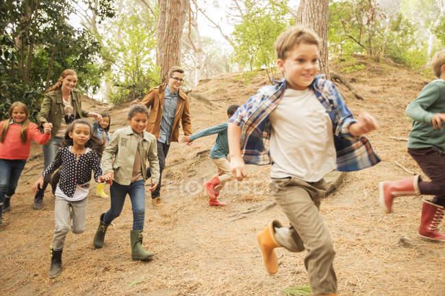 Crianças que correm na floresta durante o dia — Fotografia de Stock